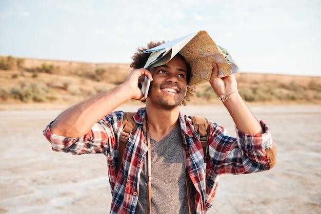 Счастливый афро-американский молодой человек покрыл голову картой и разговаривает по мобильному телефону