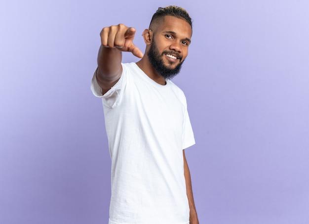 흰색 티셔츠를 입은 행복한 아프리카계 미국인 청년은 파란 배경 위에 밝게 서서 카메라를 향해 검지 손가락으로 가리키고 있습니다.
