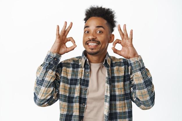 행복한 아프리카계 미국인 청년, ok 사인을 보여주고 승인에 고개를 끄덕이고, 만족스럽게 웃고, 훌륭한 일을 칭찬하고, 백인에 대해 승인하고 칭찬합니다. 복사 공간