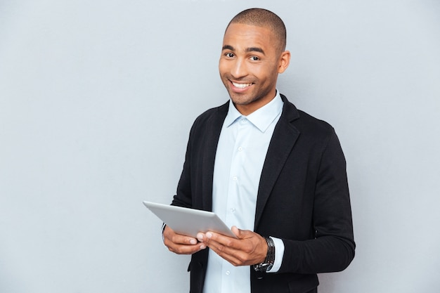 Happy african american young man smiling and using tablet
