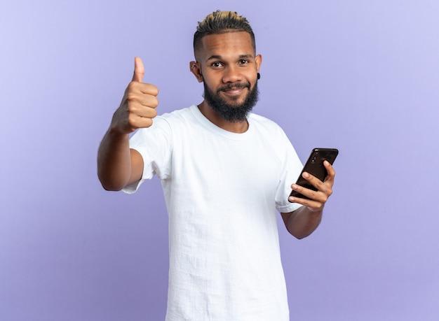 Felice giovane afroamericano con una maglietta bianca che tiene in mano uno smartphone che guarda la telecamera che mostra i pollici in su sorridendo allegramente