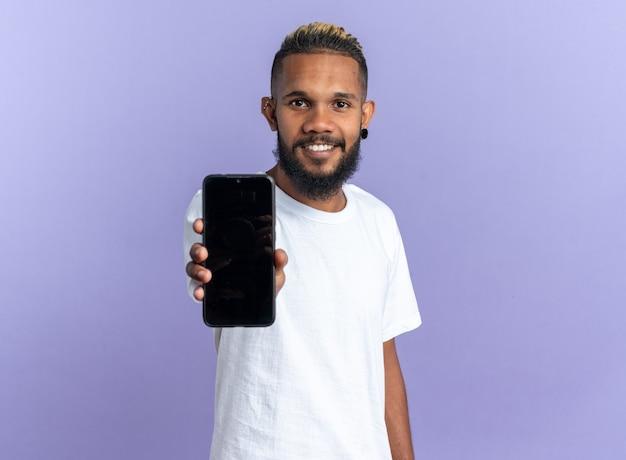 Felice giovane afroamericano in maglietta bianca che mostra smartphone guardando la telecamera sorridendo allegramente