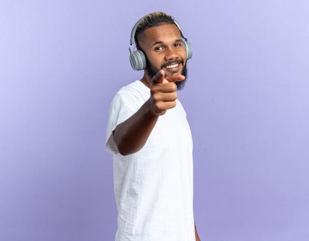 Felice americano africano giovane in bianco t-shirt con le cuffie puntate con il dito indice in telecamera sorridente allegramente in piedi su sfondo blu
