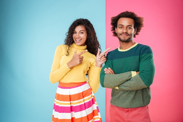 Happy african american young woman pointing on her boyfriend standing with arms crossed