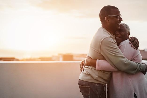 夏の日没で屋外で踊る幸せなアフリカのカップル-男の顔に焦点を当てる