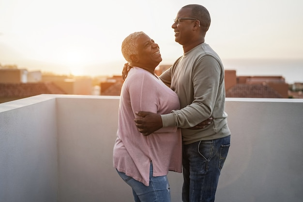 Happy african couple dancing outdoors at sunset - soft focus on man face