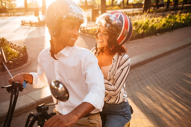 Happy african couple rides on modern motorbike in park and looking to each other