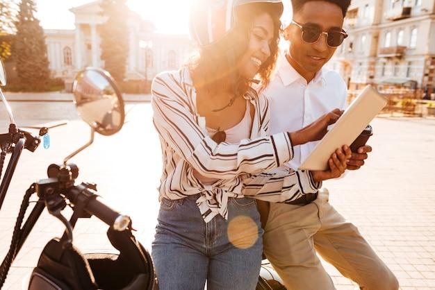 Счастливая пара африканских, сидя на современном мотоцикле и с помощью планшетного компьютера на улице