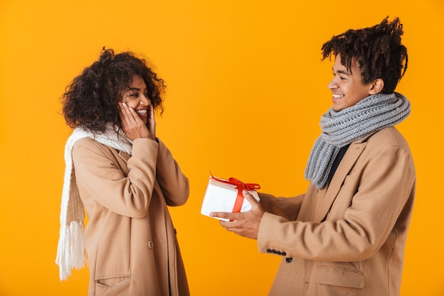 Happy african couple wearing winter clothes standing isolated, giving presents