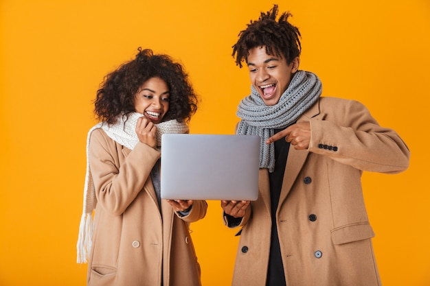 Happy african couple wearing winter clothes standing isolated, holding laptop computer, celebrating success