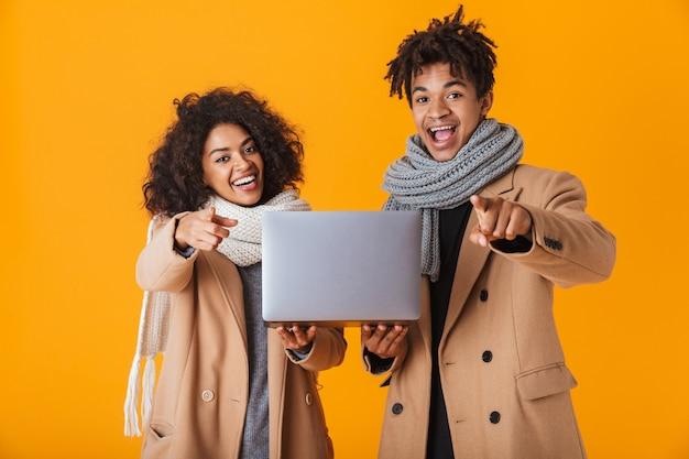 Счастливая африканская пара в зимней одежде стоя изолированно, держа портативный компьютер, указывая вперед