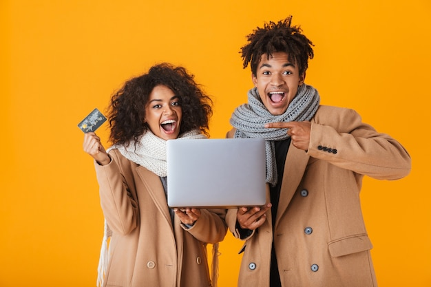 Happy african couple wearing winter clothes standing isolated, holding laptop computer, showing plastic credit card, celebrating