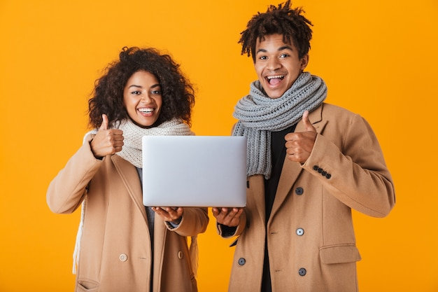 Happy african couple wearing winter clothes standing isolated, holding laptop computer, thumbs up