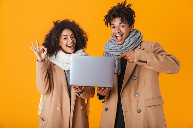 Happy african couple wearing winter clothes standing isolated, holding laptop computer