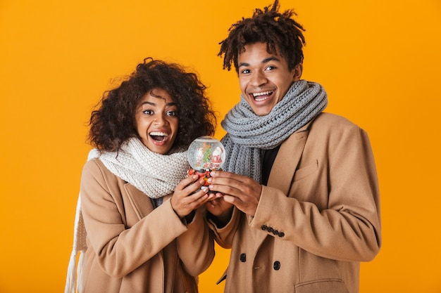 Happy african couple wearing winter clothes standing isolated, holding snowglobe