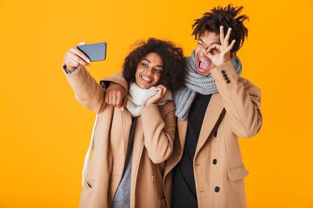 Happy african couple wearing winter clothes standing isolated, taking a selfie