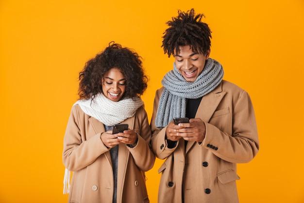 겨울 옷을 입고 행복 한 아프리카 커플 격리 된 서, 휴대 전화를 사용 하여