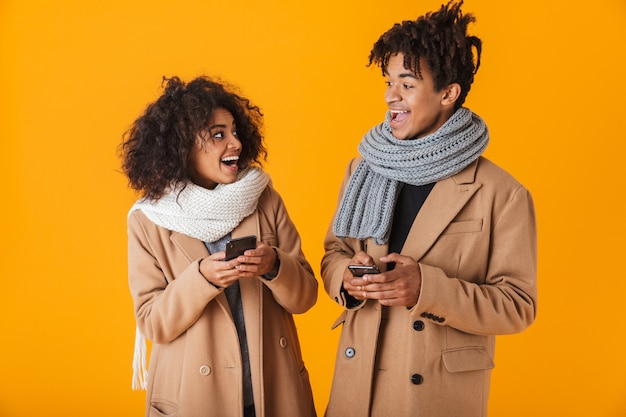 Счастливая африканская пара в зимней одежде стоя изолированно, используя мобильные телефоны