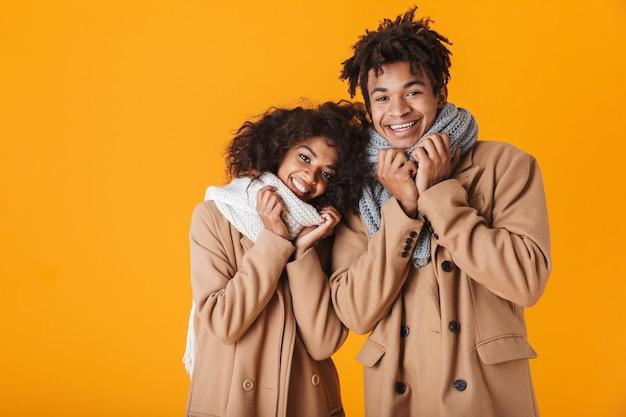 孤立して立っている冬の服を着て幸せなアフリカのカップル