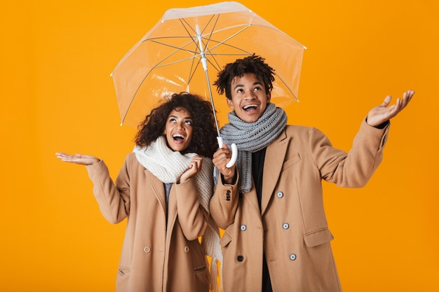 Happy african couple wearing winter clothes standing under an umbrella isolated
