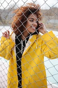 屋外のフェンスの近くに立って幸せなアフリカの巻き毛の若い女性 無料写真