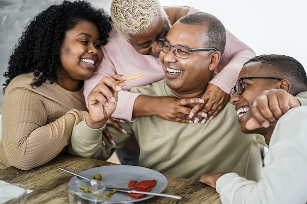 Happy african family eating lunch together at home - main focus on boy face