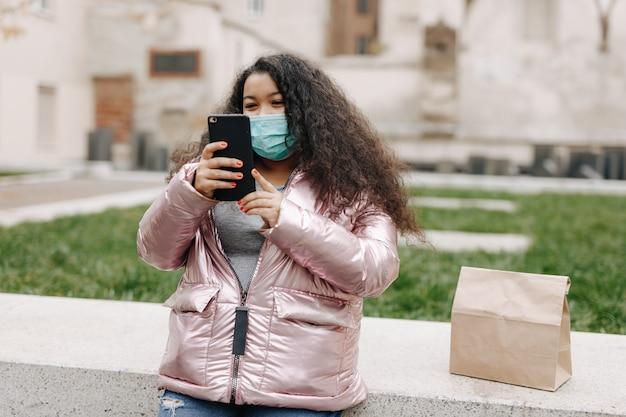 市内中心部に立ってスマートフォンでビデオチャットをしている医療マスクの幸せなアフリカの女性。距離会話と技術の概念。
