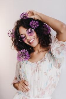 目を閉じて笑っている短い髪の幸せなアフリカの女性モデル。紫色の花でポーズをとって喜んでいる黒人の女の子の屋内写真。