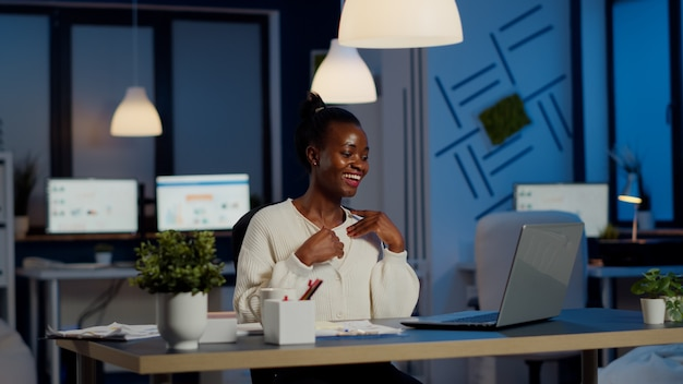 Happy african freelancer receving good news on laptop working overtime in start up company office