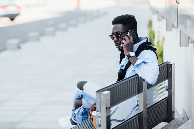 Happy african freelancer speak by phone on street, while sitting on the stairs.