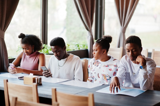 Happy african friends sitting and chatting in cafe. group of black peoples meeting in restaurant and look at their mobile phone.