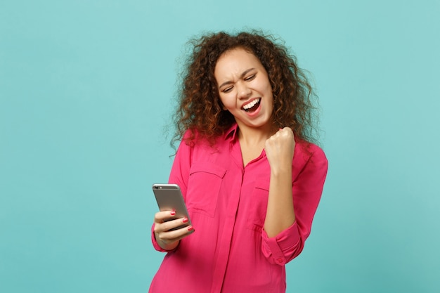 Happy african girl in casual clothes doing winner gesture, using mobile phone, typing sms message isolated on blue turquoise background. people sincere emotions, lifestyle concept. mock up copy space.