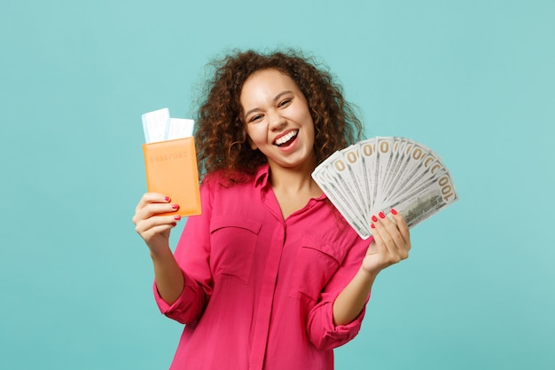 행복한 아프리카 소녀는 파란색 청록색 배경에 격리된 달러 지폐 현금 돈을 좋아하는 여권 탑승권을 들고 있습니다. 사람들은 진심 어린 감정 라이프 스타일 개념입니다. 복사 공간을 비웃습니다.