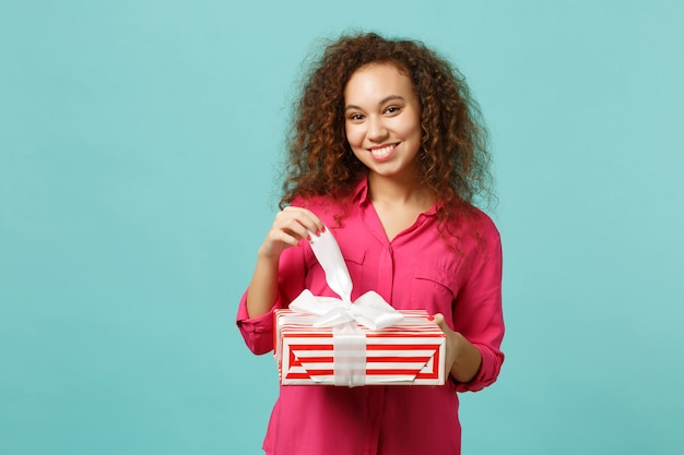 カジュアルな服装で幸せなアフリカの女の子は、青いターコイズブルーの壁の背景に分離されたギフトリボンと赤い縞模様のプレゼントボックスを保持します。国際女性の日の誕生日の休日の概念。コピースペースをモックアップします。