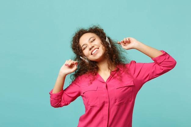 青いターコイズブルーの壁の背景に分離されたヘッドフォンで音楽を聴きながら、目を閉じてカジュアルな服を着て幸せなアフリカの女の子。人々の誠実な感情、ライフスタイルのコンセプト。コピースペースをモックアップします。