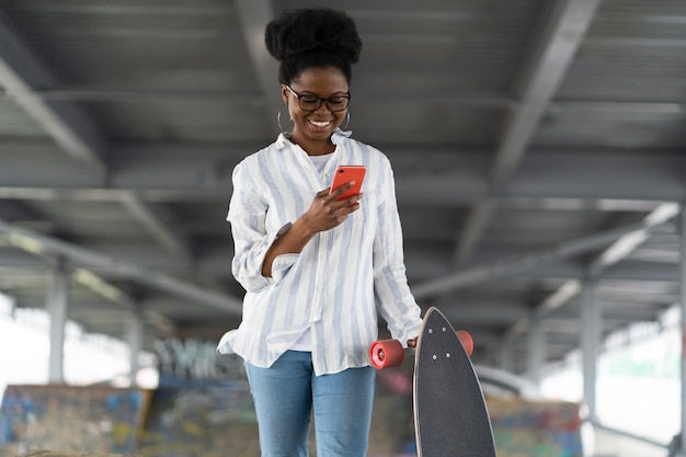 Happy african girl skater with longboard use smartphone for chatting or watching video connect to g