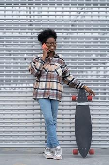 행복한 아프리카 소녀는 친구와 대화를 나누며 스마트폰 여성을 사용하여 휴대폰으로 대화를 즐깁니다.