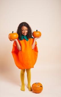 Счастливая африканская девушка с тыквами на хэллоуин