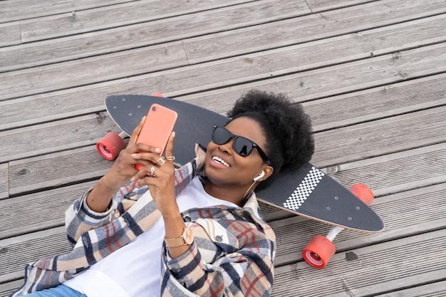 스케이트보드 위 도시 공간 바닥에 누워 스마트폰으로 롱보드 문자를 보내는 행복한 아프리카 소녀