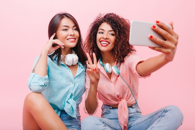 Happy african girl with pretty face posing with peace sign near charming female friend. aforable mulatto woman in jeans and pink shirt making selfie with stylish hispanic lady.