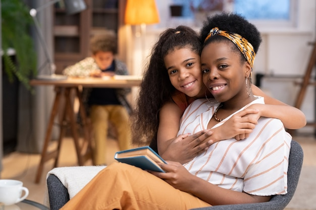 Happy african girl with toothy smile embracing her mother sitting in armchair in front of camera on background of cute boy doing homework