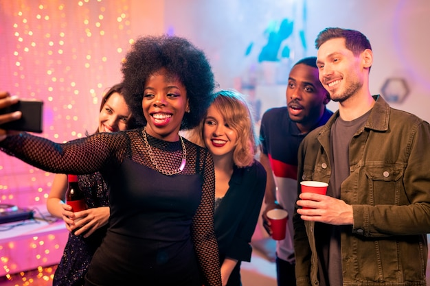 Счастливая африканская девушка с зубастой улыбкой делает селфи с межкультурными друзьями, наслаждаясь домашней вечеринкой и вместе выпивая