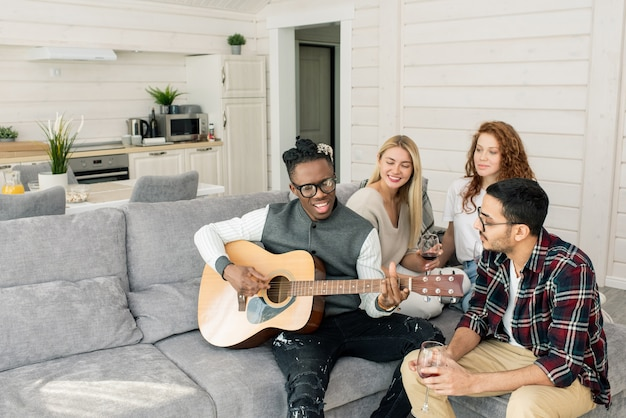 Happy african guy singing by guitar while sitting on couch among his friends with glasses of wine in home environment