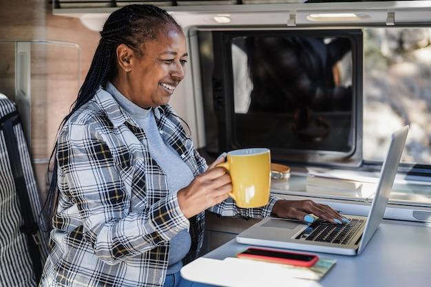 ミニキャンピングカーの中でコンピューターのラップトップを使用して楽しいアフリカの女性を楽しんで幸せ-顔に焦点を当てる