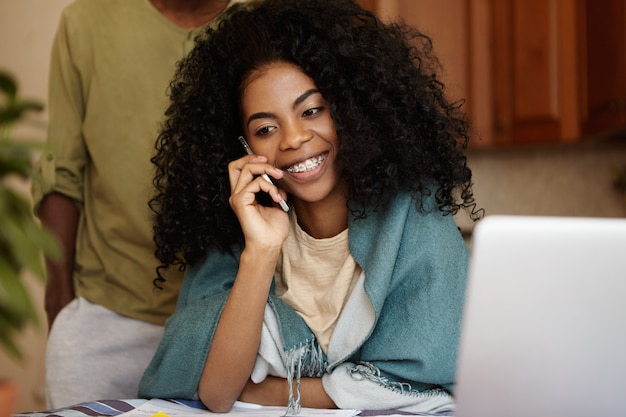 Happy african housewife holding mobile phone and talking to her friend, sitting at kitchen table, managing family finances, using laptop pc, her husband standing behind her with hands in pockets