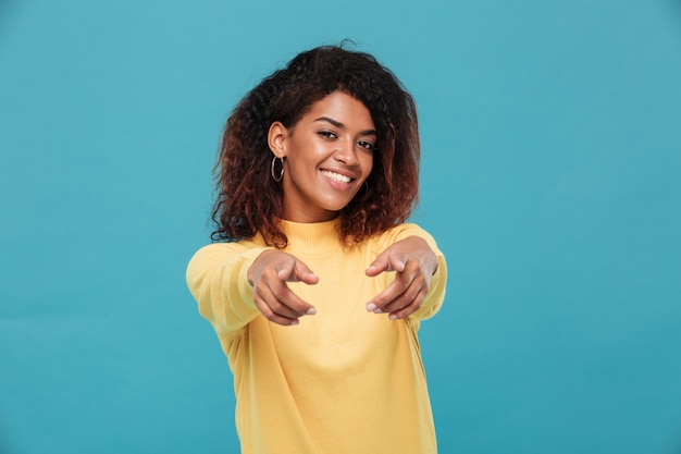 Счастливая африканская дама одета в теплый свитер, указывая на вас.