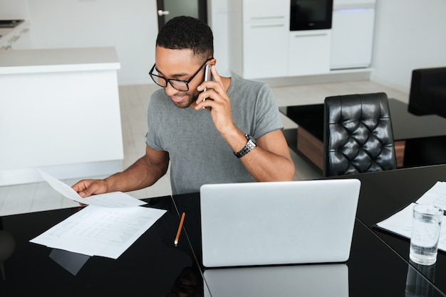 Happy african man dressed in grey t-shirt and wearing eyeglasses talking on cellphone while using laptop and looking on papers.