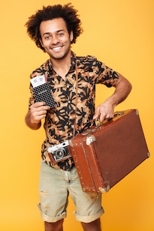 Happy african man holding passport and suitcase.