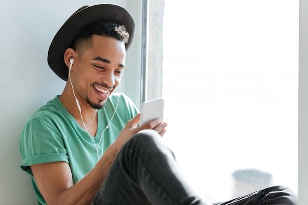 窓の近くの音楽を聴いて幸せなアフリカ人