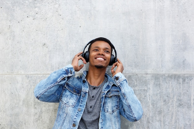 Happy african man listening to music with hands to headphones